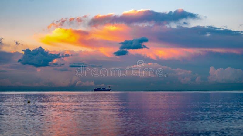 Buque de carga en el mar durante puesta del sol fotografía de archivo