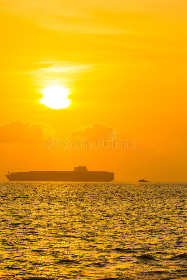 Buque de carga en el mar en la puesta del sol imagen de archivo