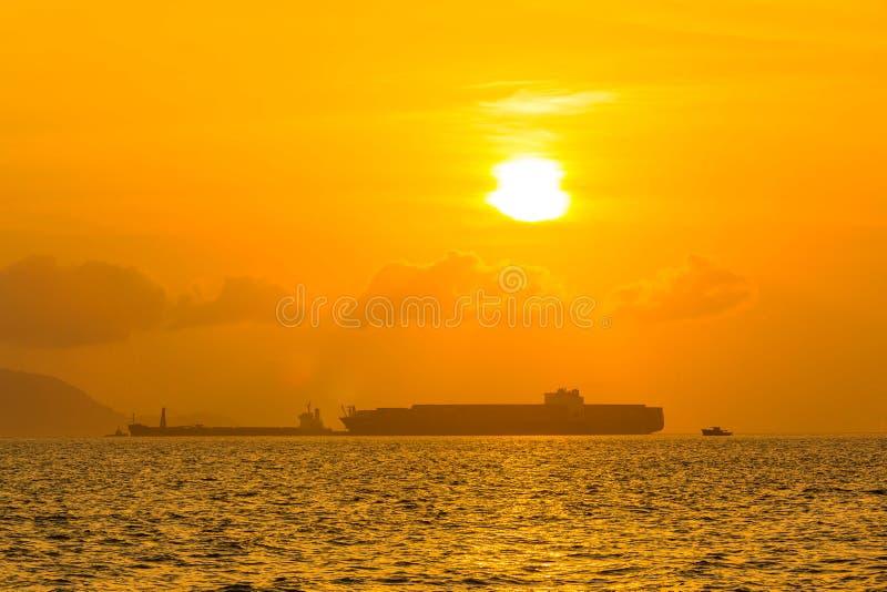 Buque de carga en el mar en la puesta del sol fotografía de archivo
