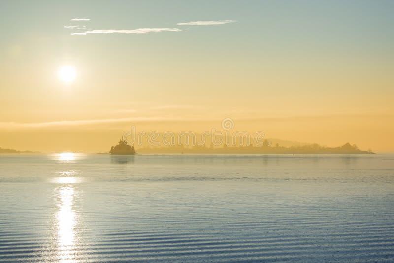 Buque de carga en la puesta del sol en el mar fotos de archivo