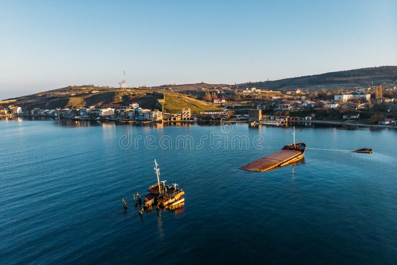 Buque de carga hundido cerca de la costa de la ciudad del mar, buque oxidado abandonado grande en el agua, visión aérea fotografía de archivo