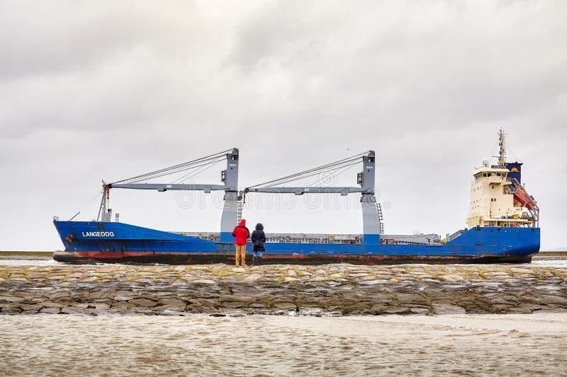 Buque de carga de Langeoog del reloj de la gente que sale del puerto de Swinoujscie imagen de archivo