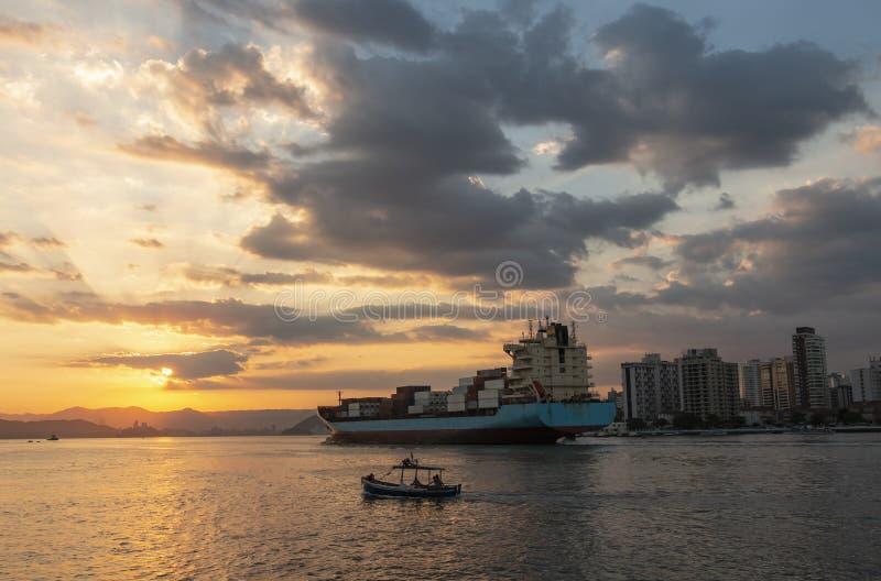 Buque de carga que sale del puerto, navegando hacia fuera al mar imagenes de archivo