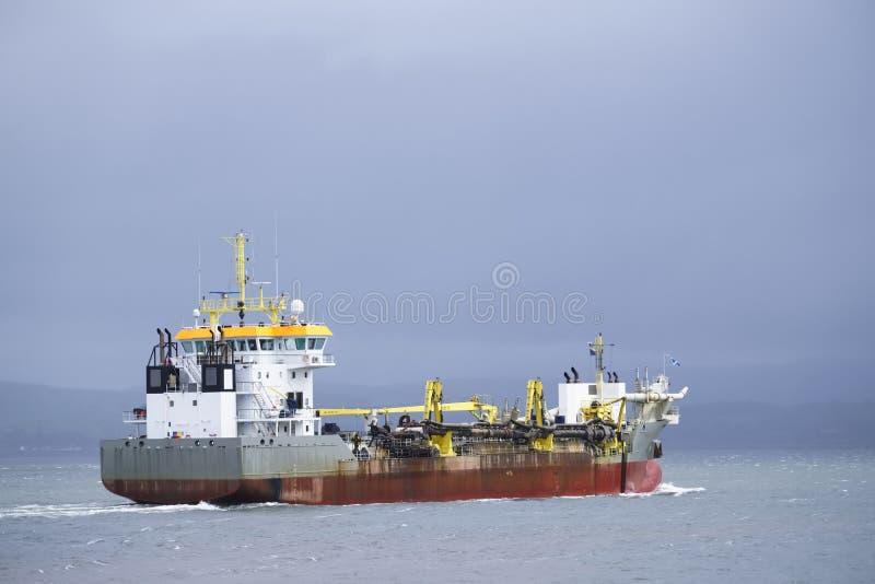 Buque de la nave del portador del envase de la exportación del cargo en el mar debajo del cielo oscuro fotografía de archivo libre de regalías