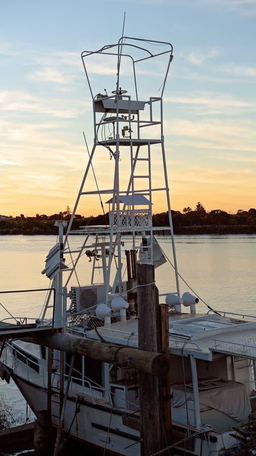 Buque pesquero amarrada para las reparaciones en la puesta del sol imagenes de archivo