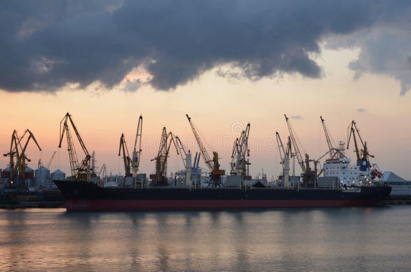 Buque y grúas de carga en el puerto, reflejado en el agua, twili imagen de archivo