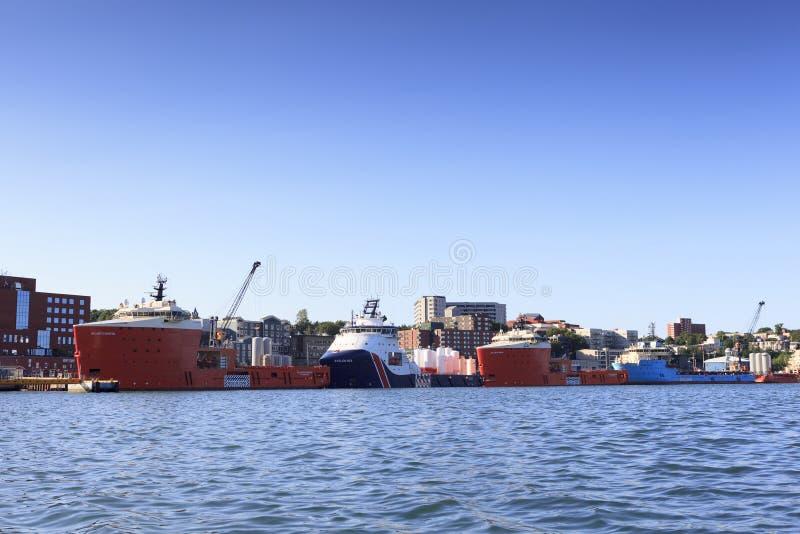 Buques costeros de la fuente en el puerto del ` s de St John imagenes de archivo