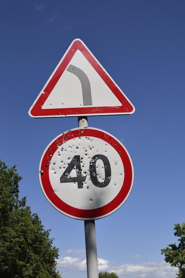 Buracos de bala no sinal de estrada do limite de velocidade imagens de stock