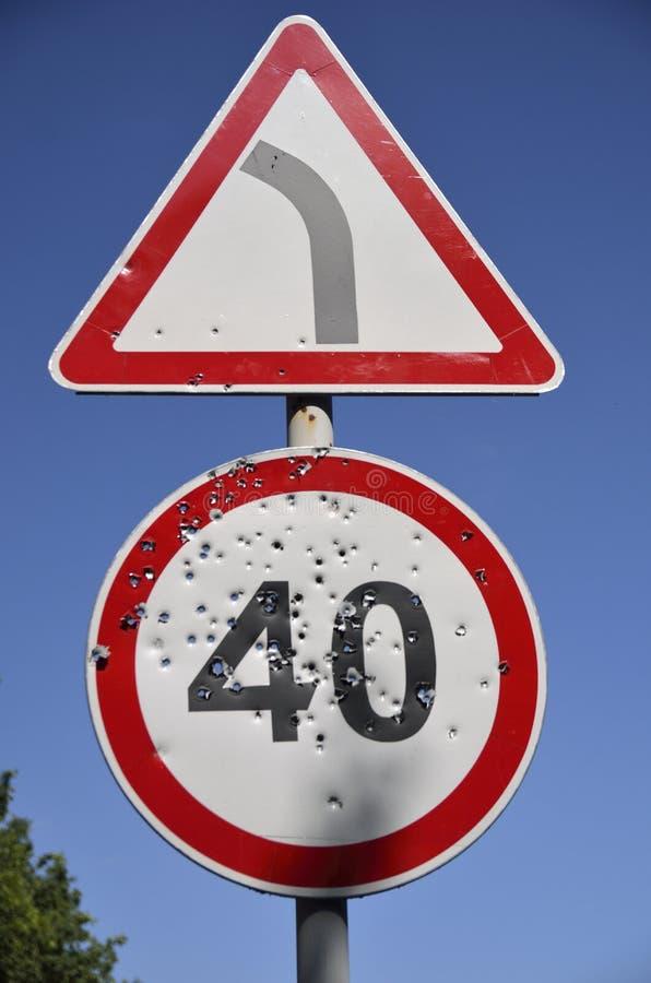 Buracos de bala no sinal de estrada do limite de velocidade fotografia de stock royalty free