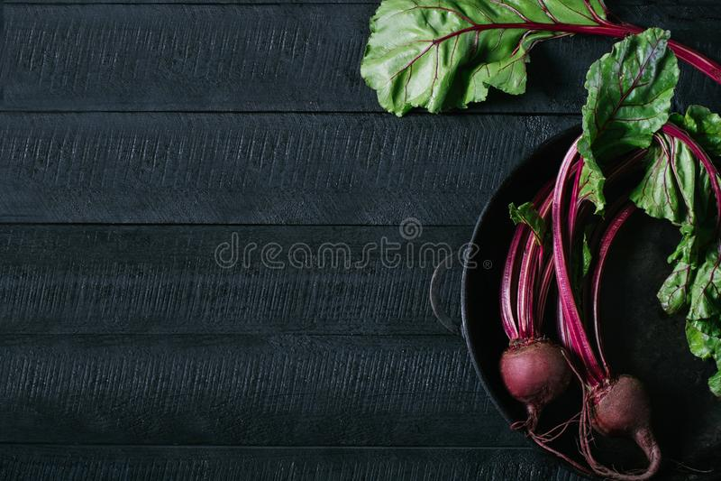 Buraki z zielonymi wierzchołkami w round metal niecce na ciemnego czerni drewnianym tle, świeży czerwony beetroot na tło kuchenne fotografia royalty free