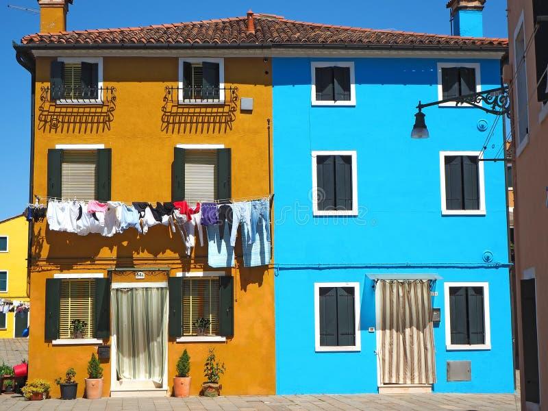 burano意大利威尼斯 有五颜六色的房子的街道有在门面的洗衣店的 免版税库存照片