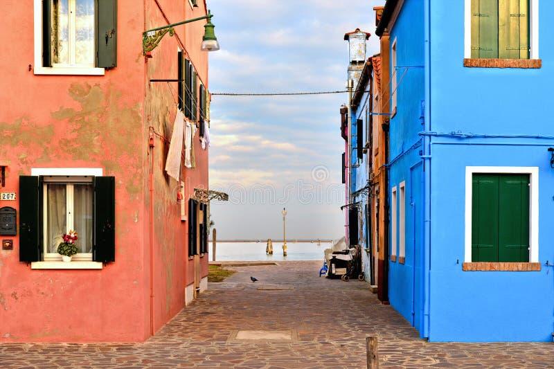 Burano海岛美丽如画的街道和庭院有小五颜六色的房子的行的反对多云天空蔚蓝和亚得里亚海 免版税库存图片