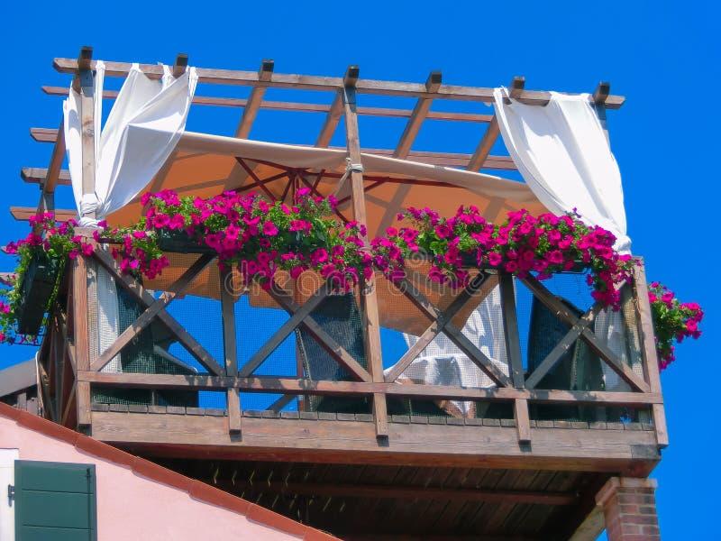 Burano, Италия - 10-ое мая 2014: Первоначально деревянная веранда с таблицей и стульями стоковое фото