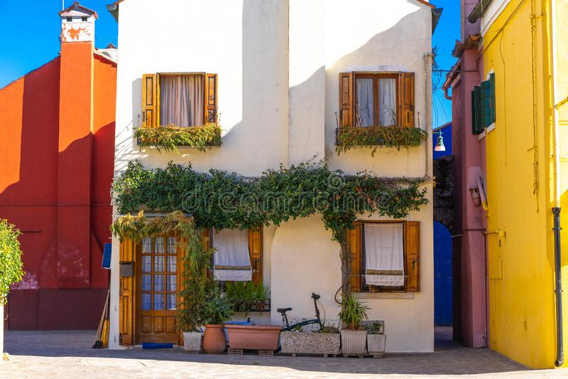 Ζωηρόχρωμα σπίτια του νησιού Burano Βενετία Χαρακτηριστική οδός με την ένωση του πλυντηρίου στις προσόψεις των ζωηρόχρωμων σπιτιώ στοκ φωτογραφία