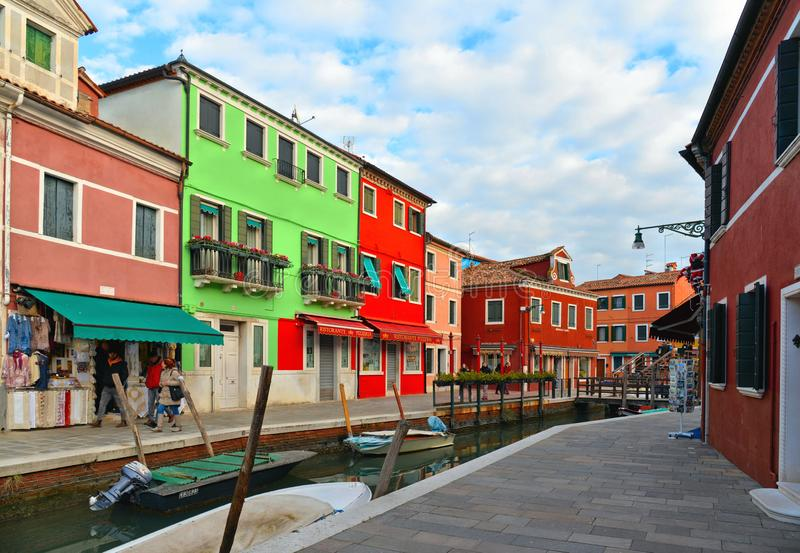 Burano island picturesque street with small colored houses in row, water canal with fishermans boats, cloudy blue sky stock photo