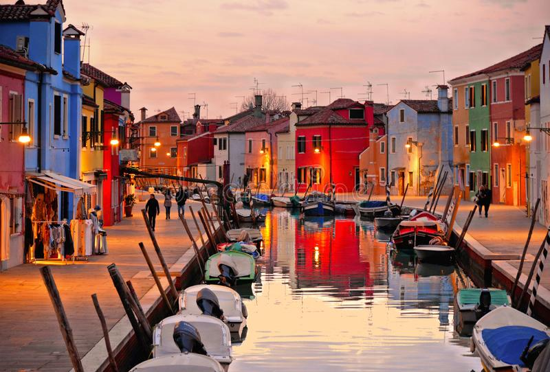 Burano island picturesque street with small colored houses, tourists on street and beautiful water reflections on cana stock image