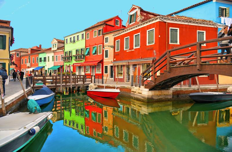 Burano island picturesque street with small colored houses, tourists on wooden bridge and beautiful water reflections stock photos