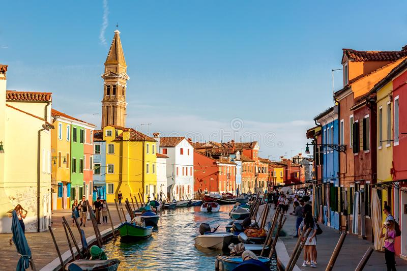 Burano island, Venice, Italy - September, 2017: Colorful houses with canal and the leaning bell tower campanile of St. Martin`s stock images
