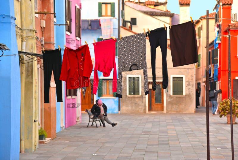 Burano, Italien Ansicht der bunten Häuser und Hof mit den Wäschereistoffen, zum der externen und älteren Frau zu trocknen entspan stockfotografie