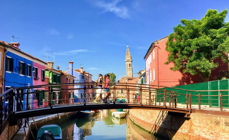 A couple of young siblings walking across a canal in Burano, Italy with old colourful homes and the leaning bell tower in the back. Burano, Italy - July 1st royalty free stock photos