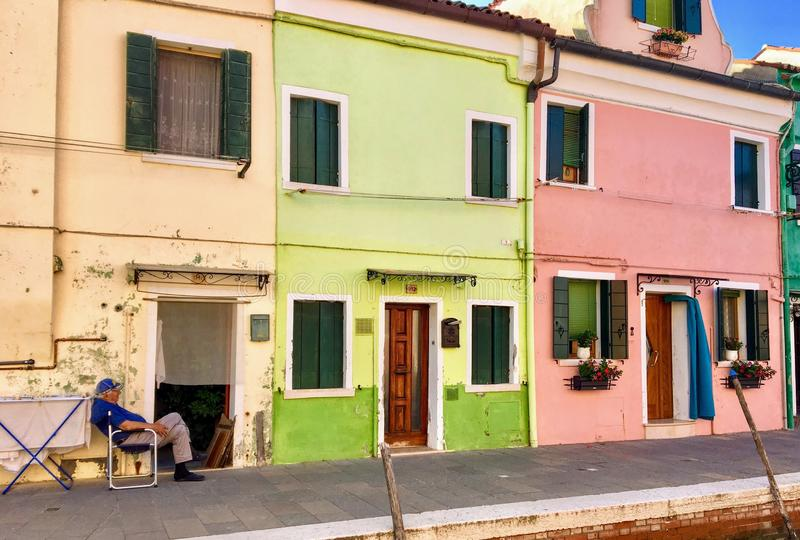 A view of a few historic colorful homes with a local man sitting outside enjoying a beautiful summer morning in Burano, Italy. royalty free stock image