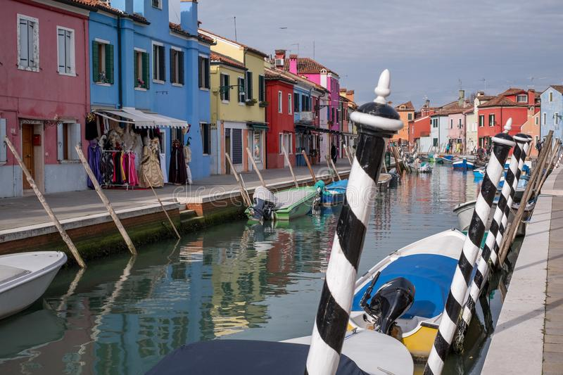 Typical street scene showing brighly painted houses, mooring posts and canal on the island of Burano, Venice. stock images