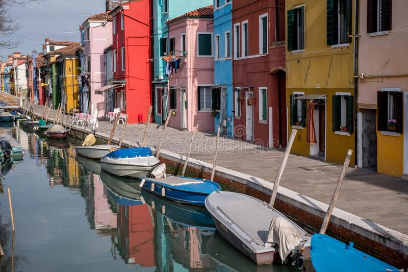 Burano, Italy. Typical street scene showing brightly painted houses reflected in the canal, with boats. stock photos