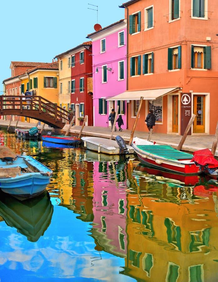 Burano wyspy malownicza ulica z małymi barwionymi domami, turystami na drewnianym moście i pięknymi wodnymi odbiciami, fotografia royalty free