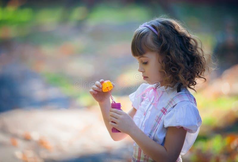 Burbuja de jabón de la niña que sopla preciosa divertida imagen de archivo