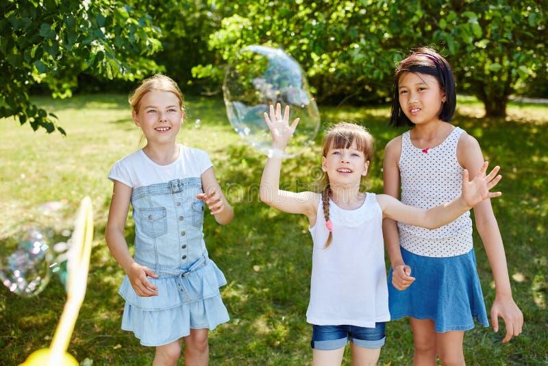 Burbujas de jabón de cogida del juego de niños imagenes de archivo