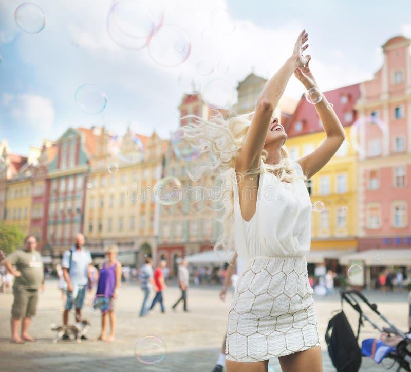 Burbujas de jabón de cogida rubias delicadas del vuelo fotos de archivo libres de regalías