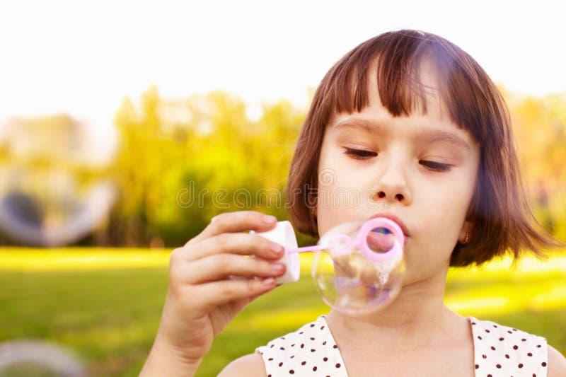 Burbujas de jabón de la muchacha que soplan imagenes de archivo