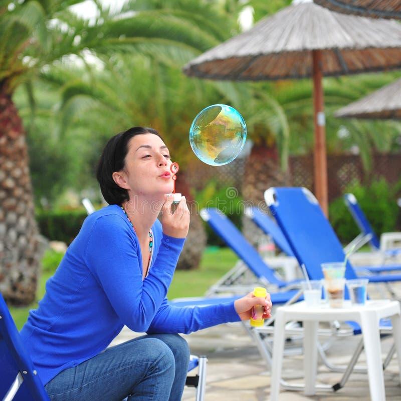 Burbujas de jabón de la muchacha que soplan hermosa joven fotografía de archivo libre de regalías