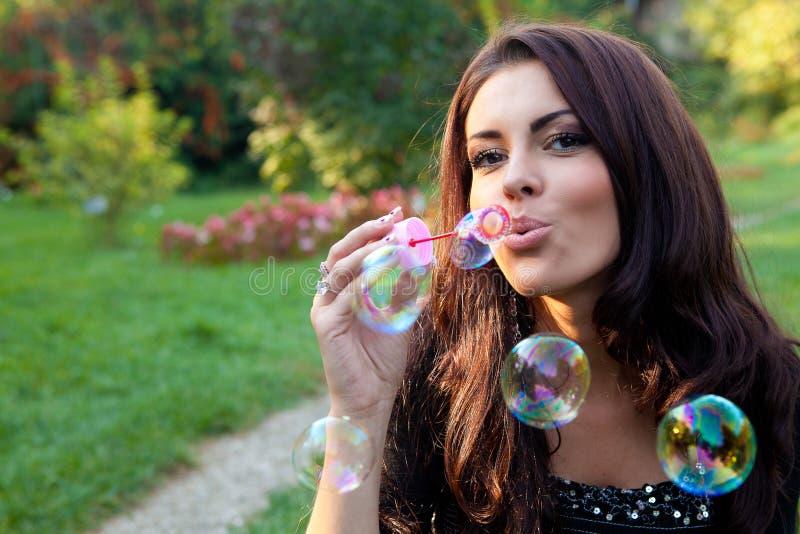 Burbujas de jabón de la mujer que soplan feliz foto de archivo libre de regalías
