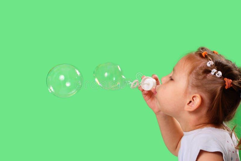 Burbujas de jabón de la niña que soplan imagen de archivo libre de regalías