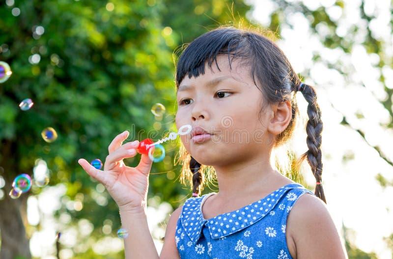 Burbujas de jabón de la niña que soplan imagen de archivo