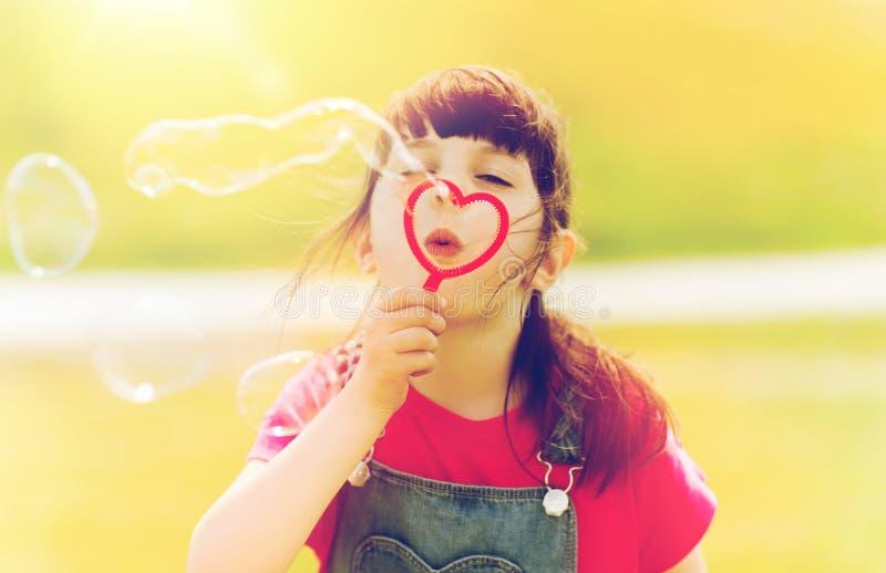 Burbujas de jabón de la niña que soplan al aire libre foto de archivo libre de regalías