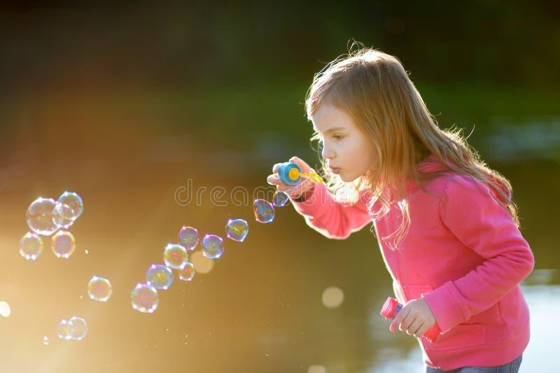 Burbujas de jabón de la niña que soplan preciosa divertida imagenes de archivo