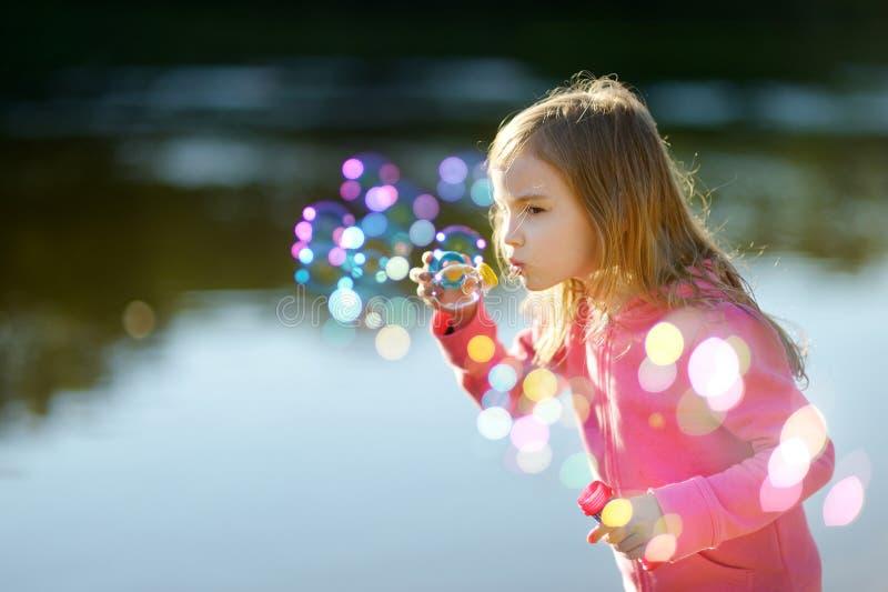 Burbujas de jabón de la niña que soplan preciosa divertida fotografía de archivo libre de regalías