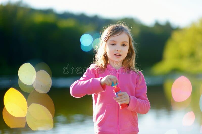 Burbujas de jabón de la niña que soplan preciosa divertida foto de archivo libre de regalías