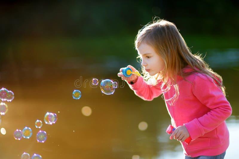 Burbujas de jabón de la niña que soplan preciosa divertida fotografía de archivo