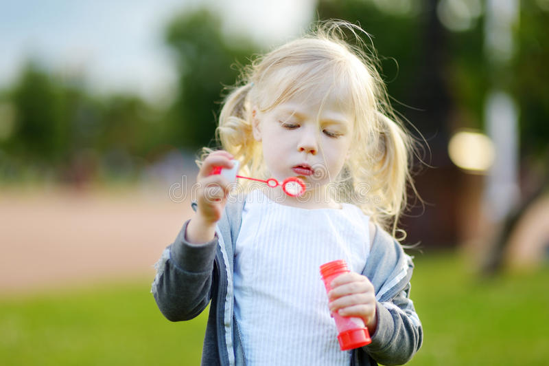 Burbujas de jabón de la niña que soplan preciosa divertida al aire libre fotografía de archivo libre de regalías