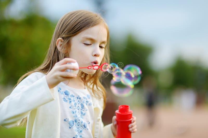 Burbujas de jabón de la niña que soplan preciosa divertida al aire libre imagen de archivo