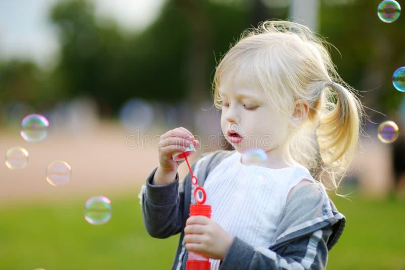 Burbujas de jabón de la niña que soplan preciosa divertida al aire libre foto de archivo libre de regalías