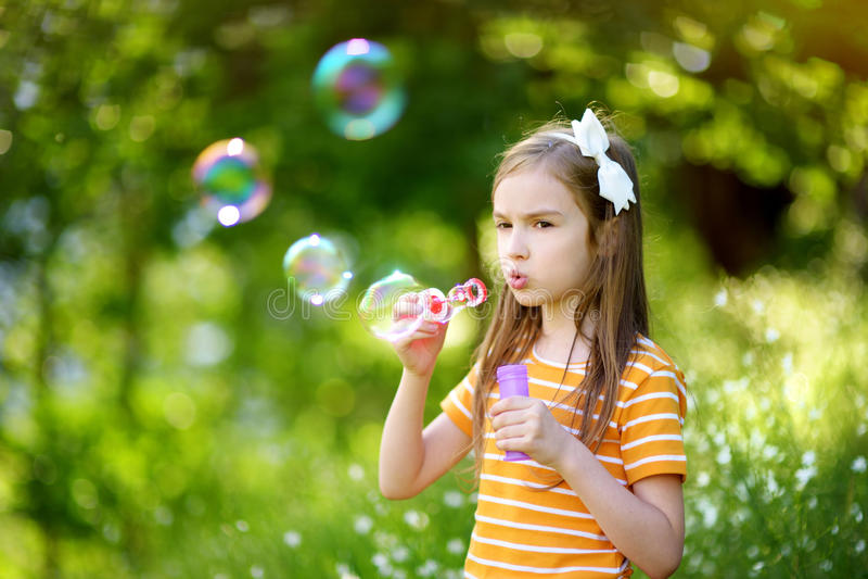 Burbujas de jabón de la niña que soplan preciosa divertida en outdors de una puesta del sol fotos de archivo