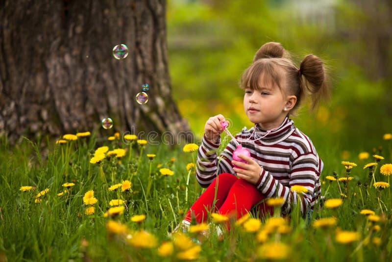Burbujas de jabón de la pequeña muchacha que soplan de cinco años foto de archivo libre de regalías