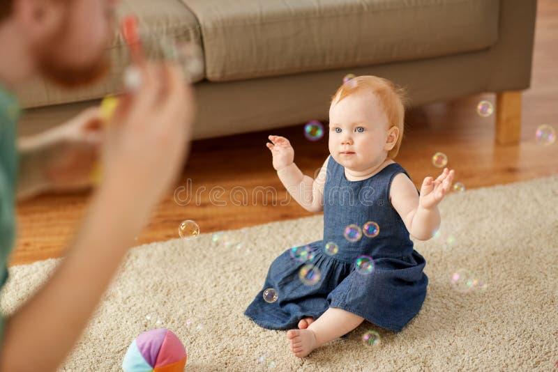 Burbujas de jabón del bebé que soplan y del padre en casa fotografía de archivo