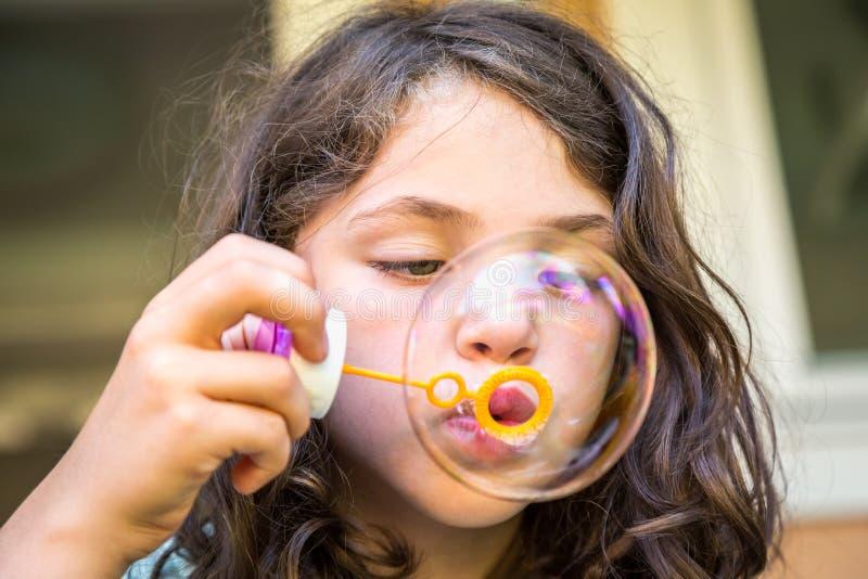 Burbujas de jabón del niño caucásico joven de la muchacha que soplan foto de archivo