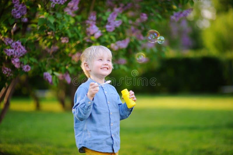 Burbujas de jabón del niño pequeño que soplan lindo en parque hermoso del verano imagen de archivo libre de regalías