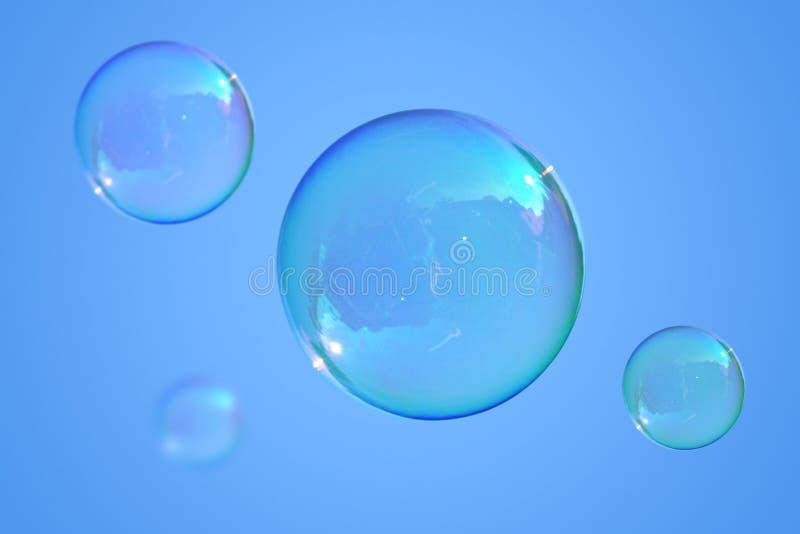 Burbujas de jabón en el cielo azul imagen de archivo